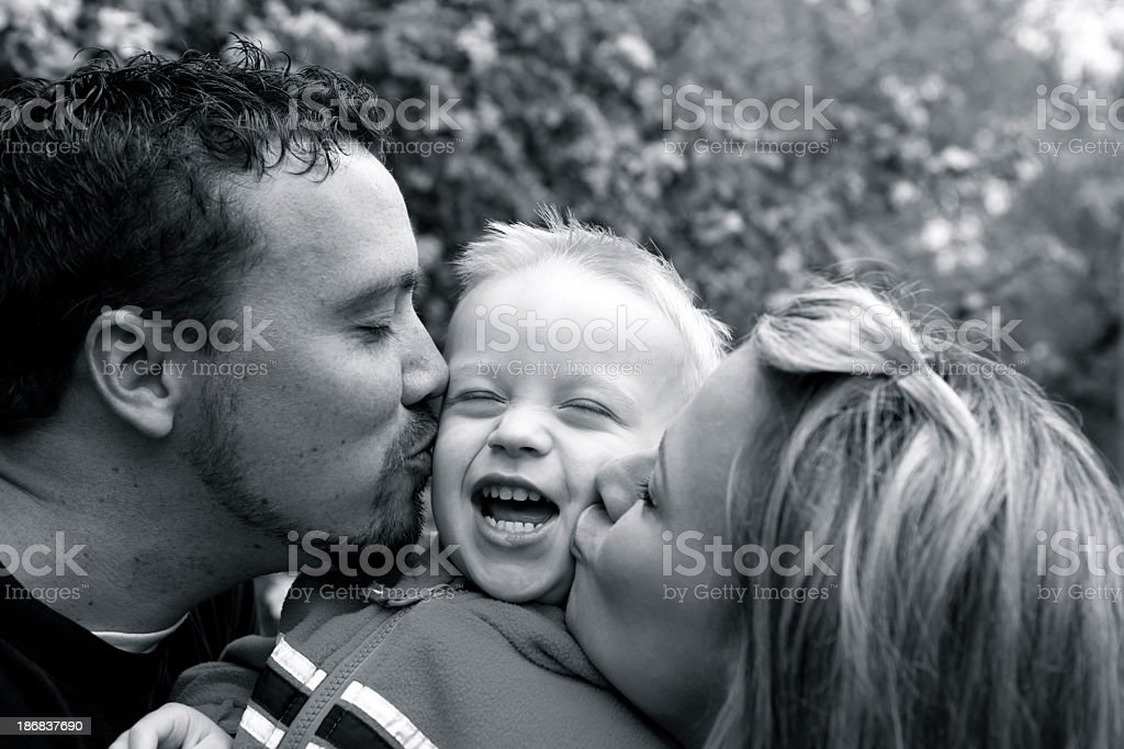 A black and white image of parents kissing a child royalty-free stock photo