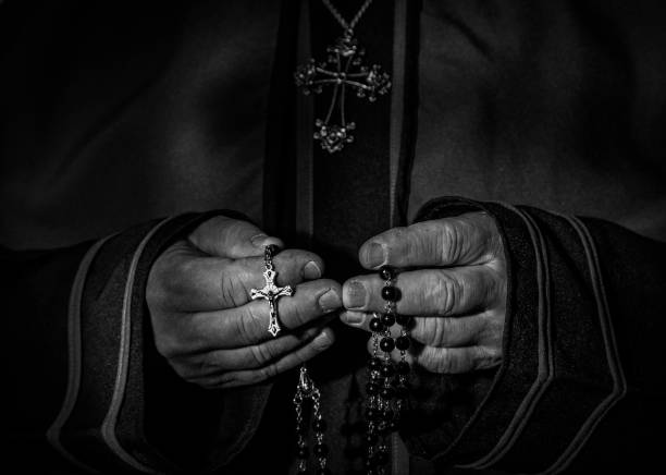black and white image of priests hands holding rosary beads stock photo