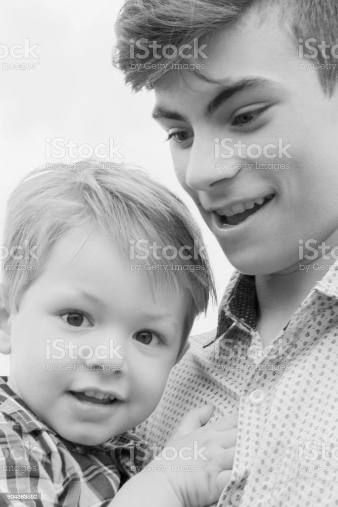 Black and White image of teenage boy with younger brother in arms walking in a field stock photo