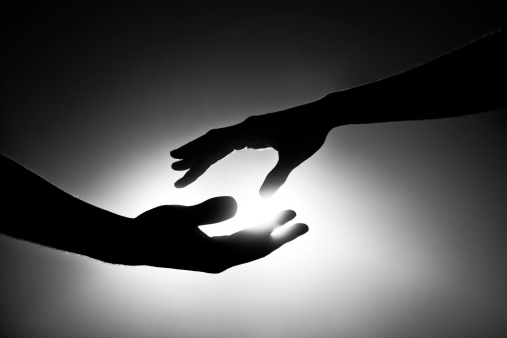 Male and female hands reaching out for each other. Black and white image with light behind them. Conceptual image that pertains to support, love, marriage and togetherness.