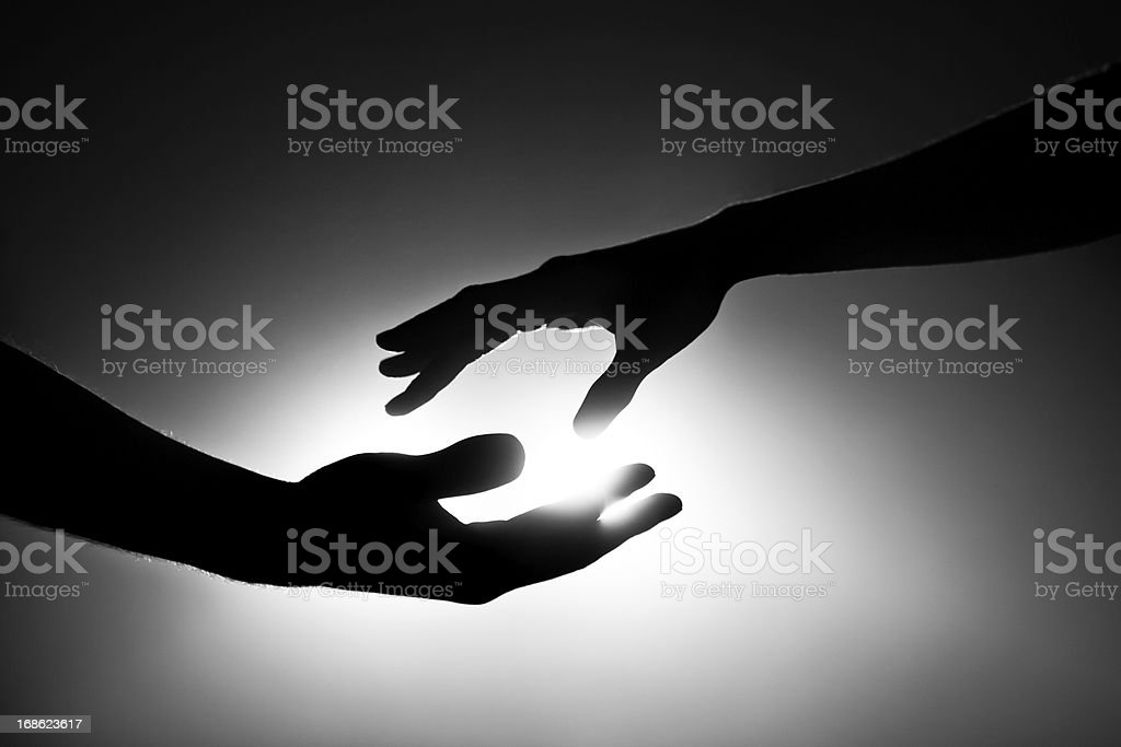 Black and white image of two hands reaching out stock photo