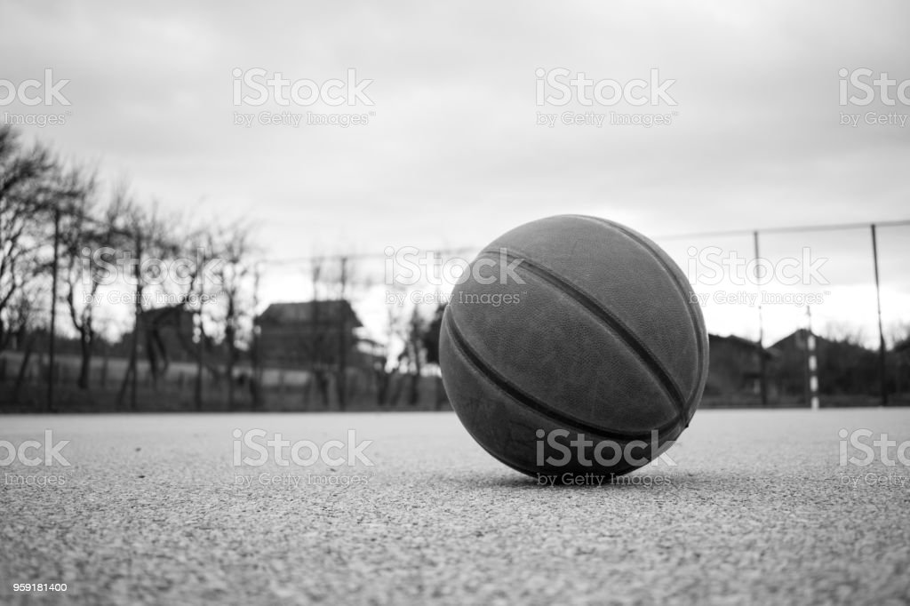 Black and white image of used orange leather basketball on grey asphalt background. stock photo