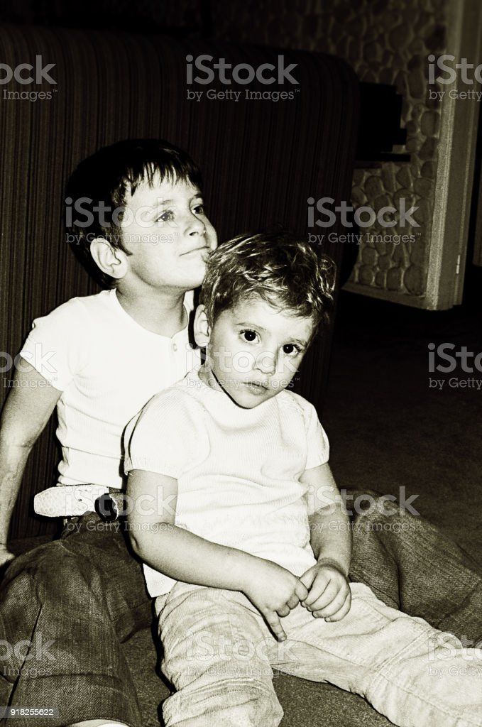 Black and white kids sitting on floor at home stock photo