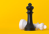 istock Black and white king chess piece isolated on pastel yellow background 1180798319