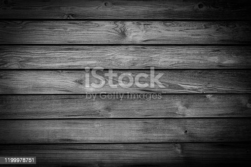 A full frame abstract background of a black and white monochrome knotted wood grain plank wall background with a rustic retro style and a dark vignette.