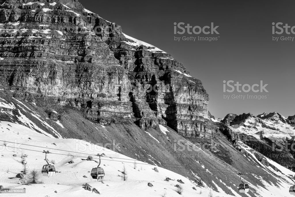 Black and white landscape. Cable car to sky resort. Massive rocks and...