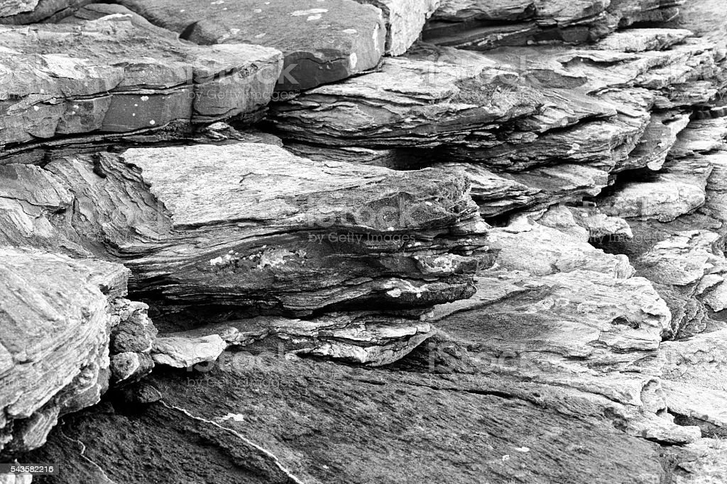 Black and white landscape of foliated rock formation at coastline stock photo