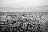 Black and white landscape. The waves on the lake. Fog and mountains