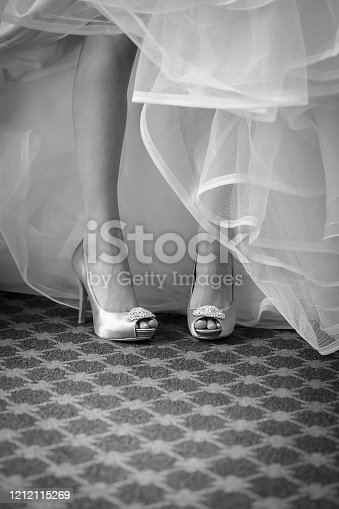 Black and white legs of bride in silk high healed pumps and tulle dress