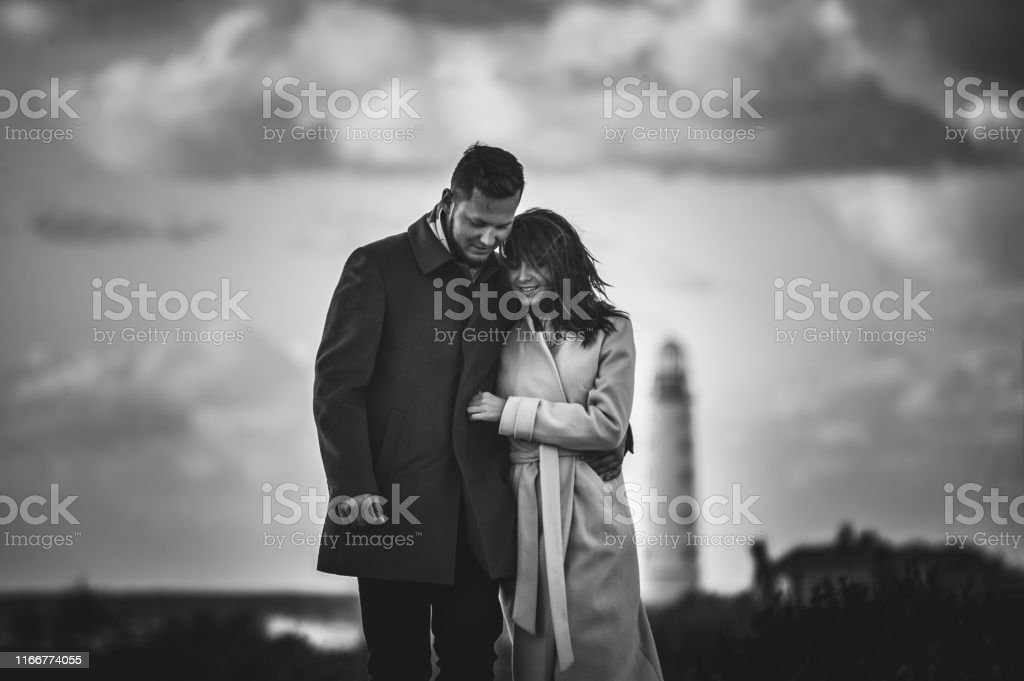 lifestyle concept of two young people man hugging woman in coat...