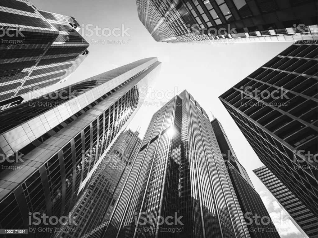 Black and White Looking Up Chicago Skyscrapers Black and White architecture shot of the modern urban skyscrapers in downtown Chicago from below. Sun reflecting in the glass facades of the urban futuristic buildings. Chicago, Illinois, USA Abstract Stock Photo
