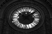 Beautiful glowing clock at night in Paris, France. Close up showing great detail and all roman numerals of clock. Black and white