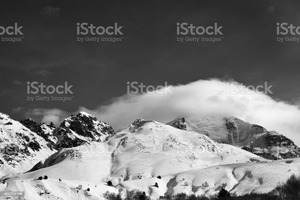 Black and white mountains in clouds and off-piste slope in winter stock photo