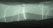 Night multi forked lightning bolt strike on hills of Goriška brda (Slovenia) with mountain Montemaggiore (Italy) - Matajure (Slovenia) in background.