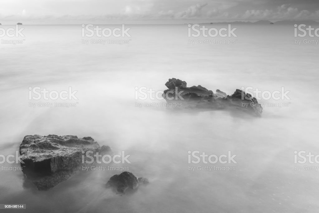 black and white mystical photo - sea waves and cobblestones on the...