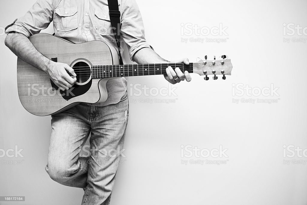 Black and white neck down view of a man playing a guitar stock photo