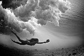 A photographer girl swims beneath breaking wave in the tropics with a camera in the waterhousing