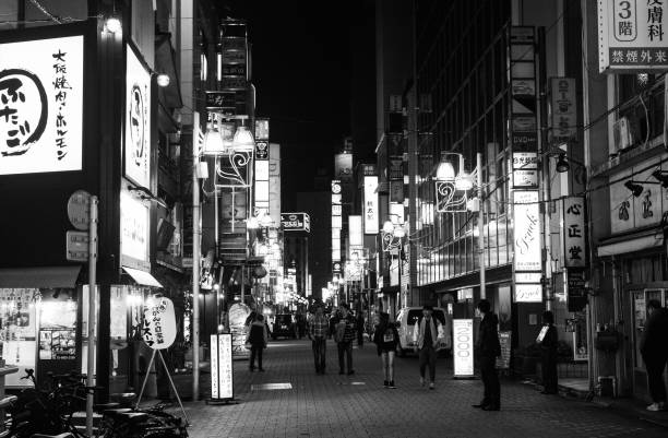 Black and white of nightlife on a busy street in Tokyo full of illuminated advertisements stock photo