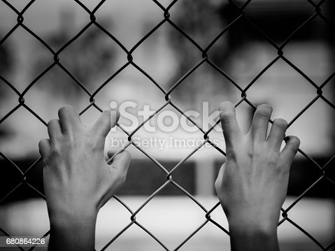 istock Black and white of Women Hands holding fence on outdoor scenery during daylight. 680864226