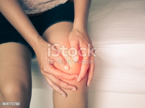 istock Black and white of young woman massaging her painful knee, Medical and health care concept. 825772730