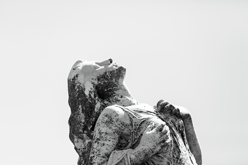 Black and white old statue of grieving young woman with hands on chest in Waverley cemetery build in 1877, the artist is unknown Sydney Australia, looking up, background with copy space, horizontal composition