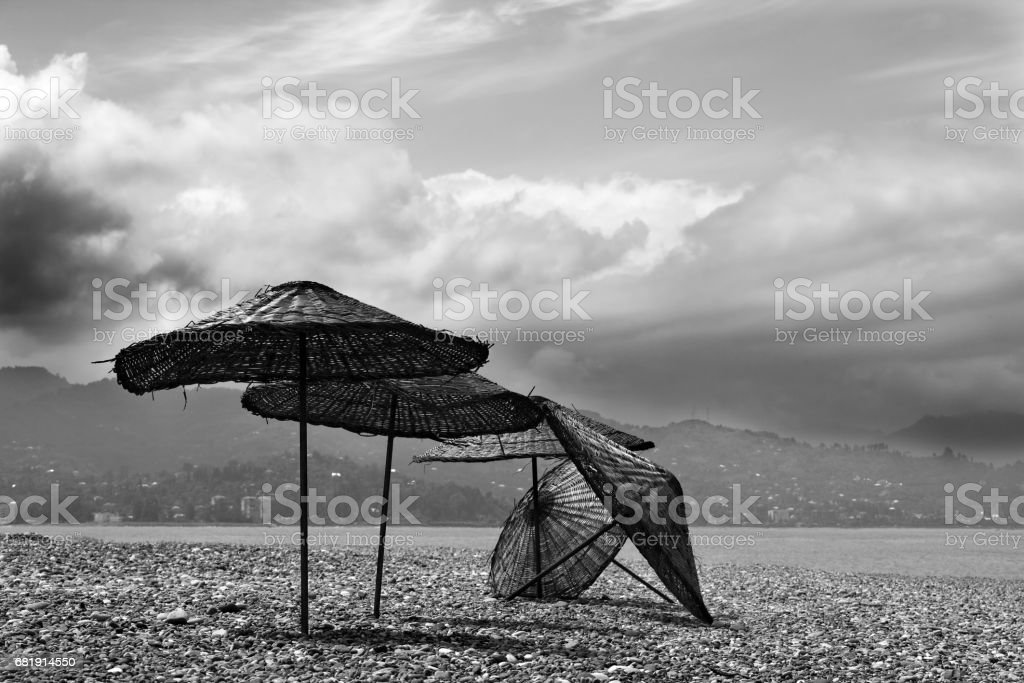 Black and white old sunshade on deserted beach out of season in sunny...