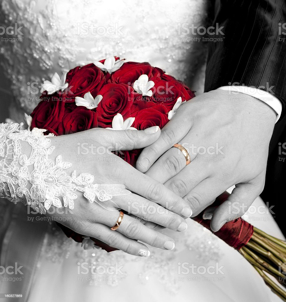 Black and white pair of hands with golden wedding rings stock photo