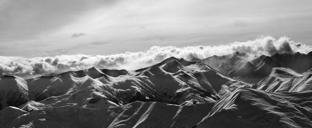 Black and white panorama of evening snow mountains at winter - foto stock