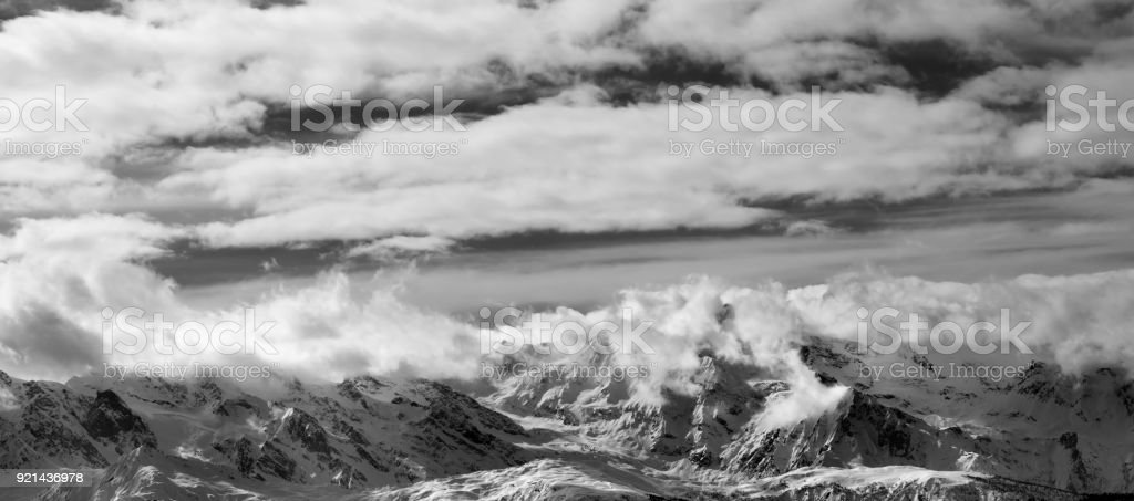 Black and white panoramic view on snow mountains and sunlight cloudy sky at winter evening stock photo