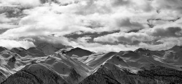 Black and white panoramic view on snowy mountains and cloudy sky in evening - foto stock