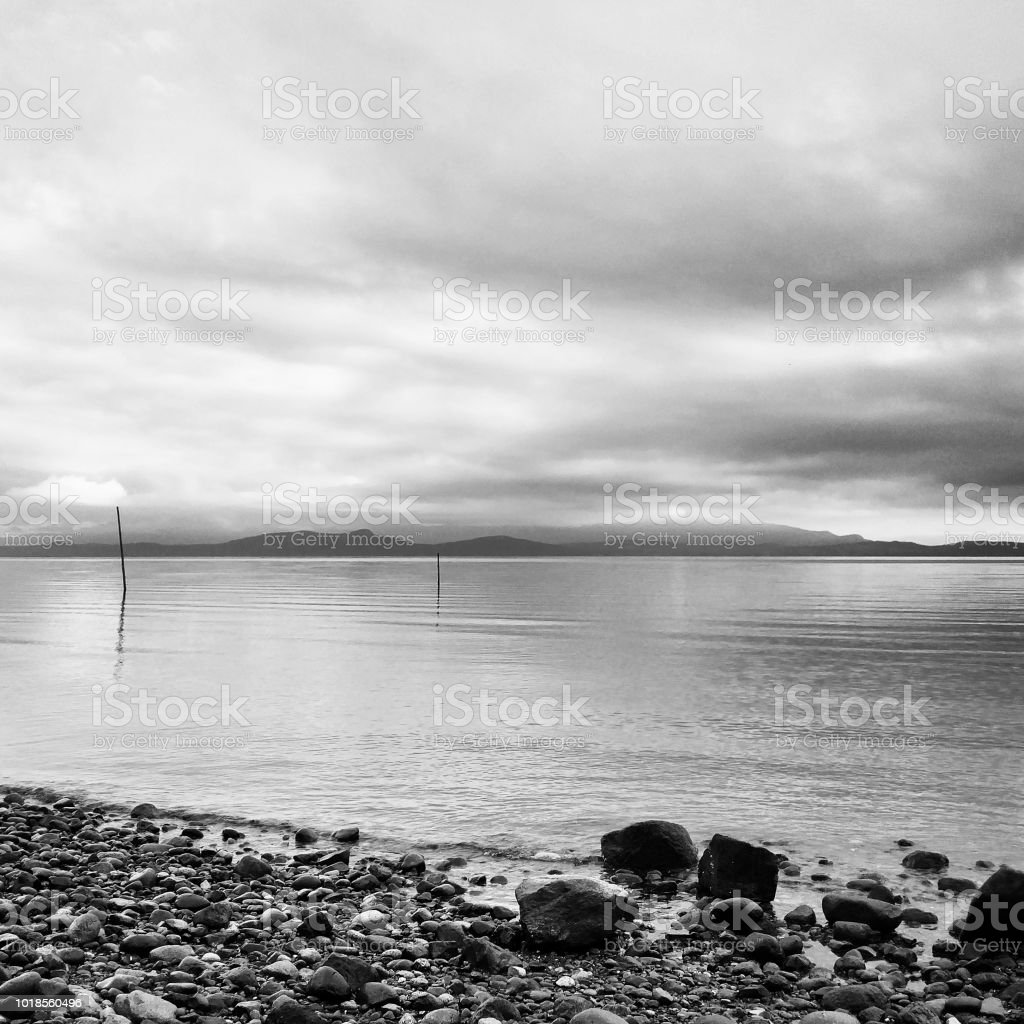 A black and white photo of a calm ocean horizon in the morning stock photo