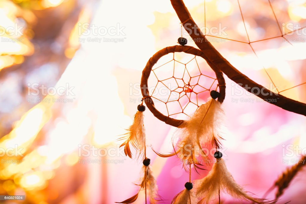 black and white photo of a dream catcher at sunset stock photo