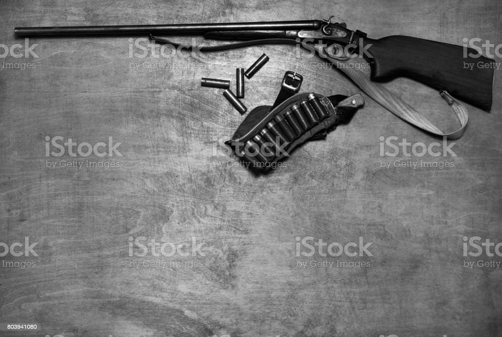 Black and white photo of a Hunting rifle, ammunition, on the wooden background with copy space, top view. stock photo