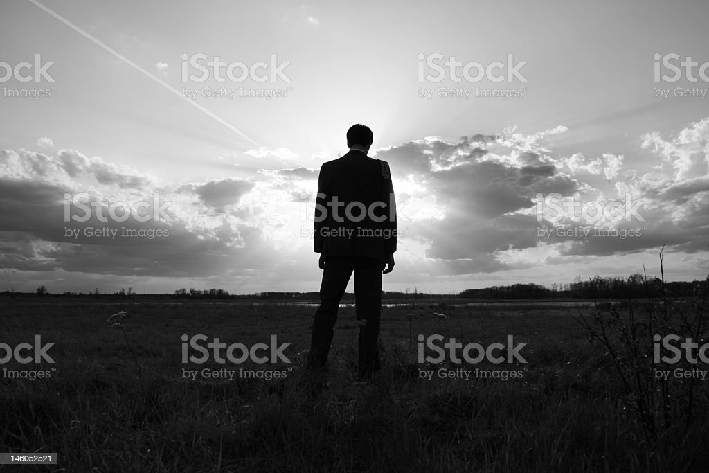 Black and white photo of a man watching the sun royalty-free stock photo