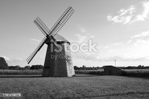 A black and white photo of a tiny wooden mill replica with enormous blades standing in the middle of a well maintained meadow, grass, or pastureland seen on a cloudy summer day on a Polish countryside