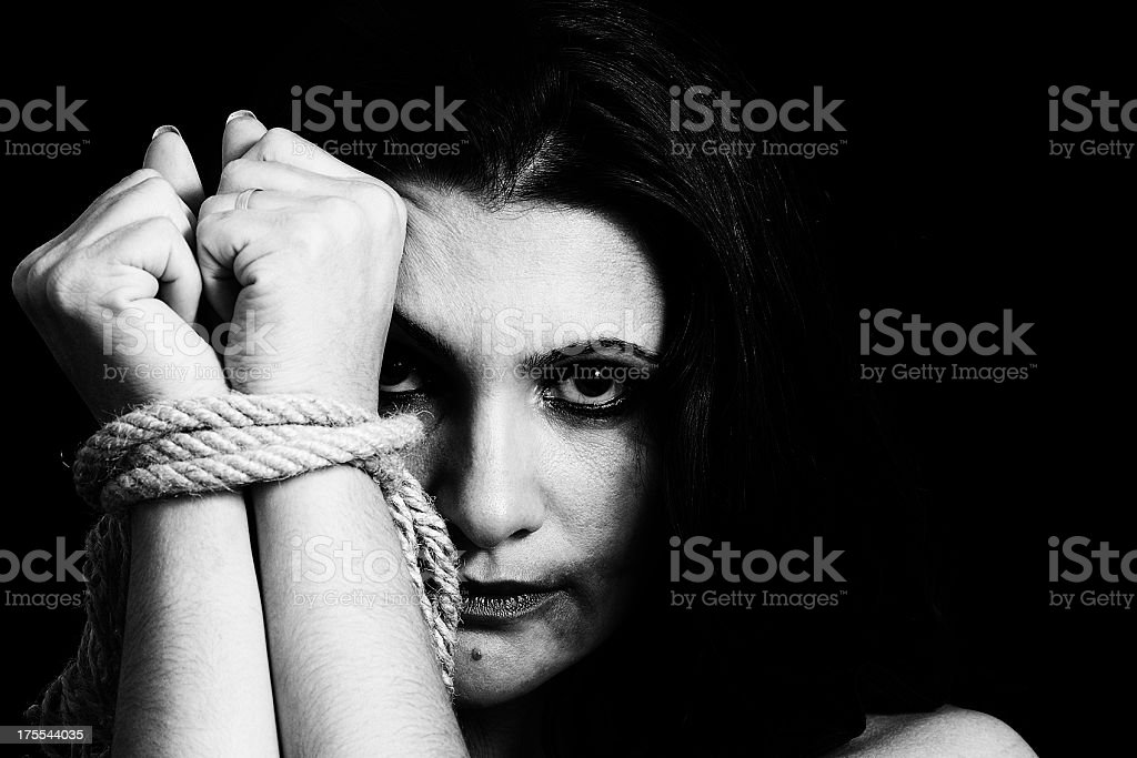 Black and white photo of a woman upset with her hands tied stock photo
