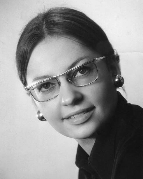 A black and white photo of a young woman in glasses stock photo
