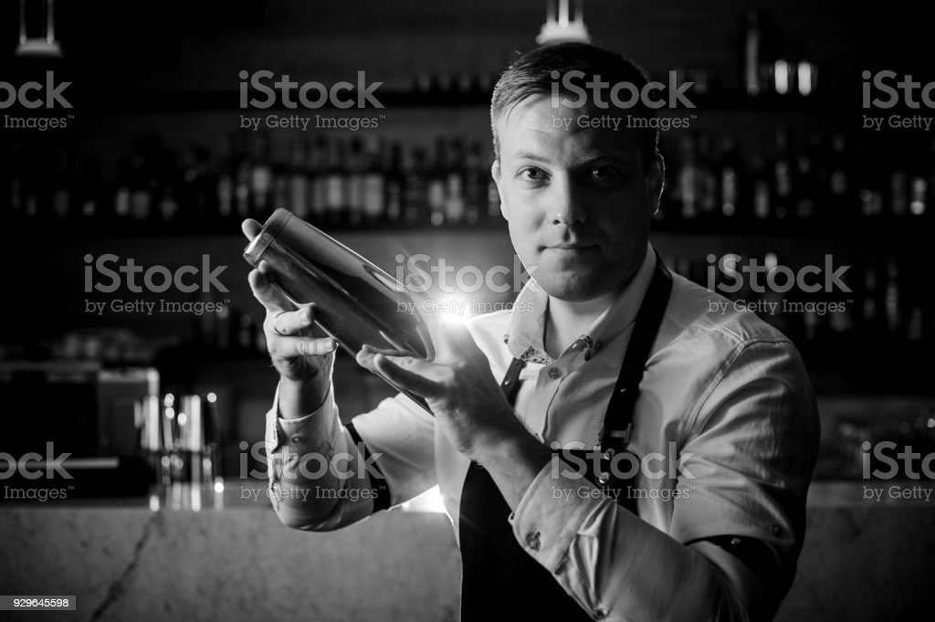 Black and white photo of barman making a cocktail using a shaker stock photo