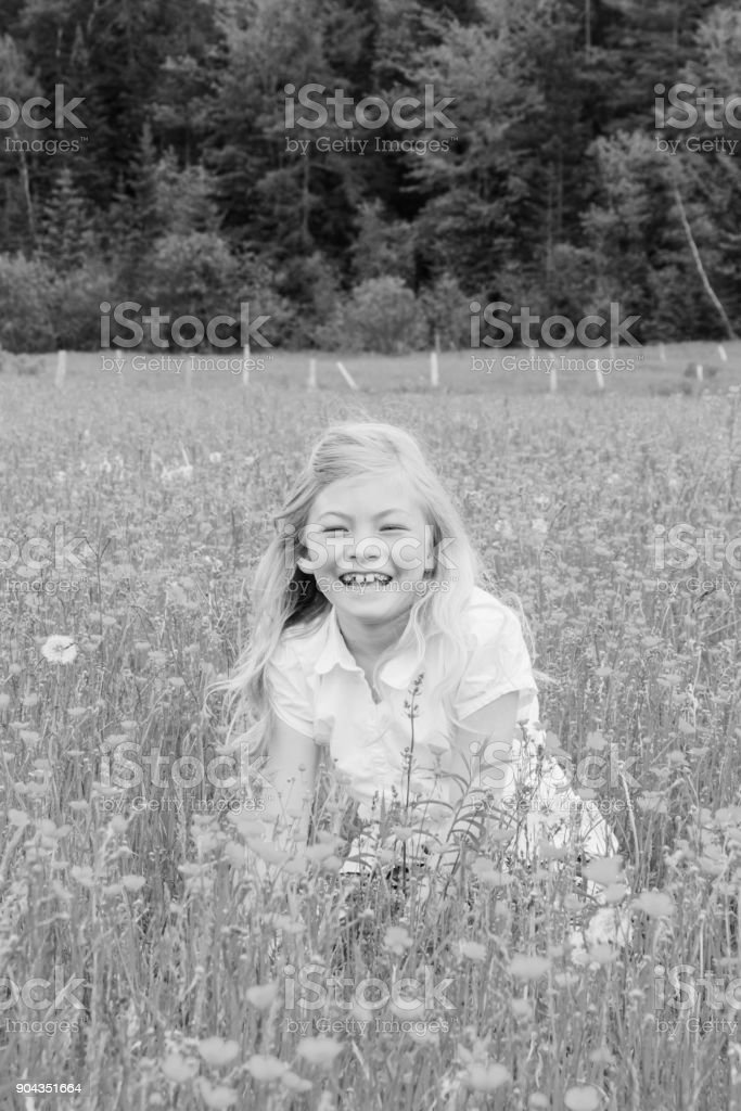 Black and white photo of blond girl smiling in a field stock photo