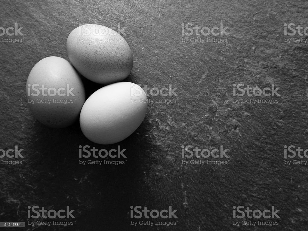 Black and white photo of brown eggs on slate stock photo