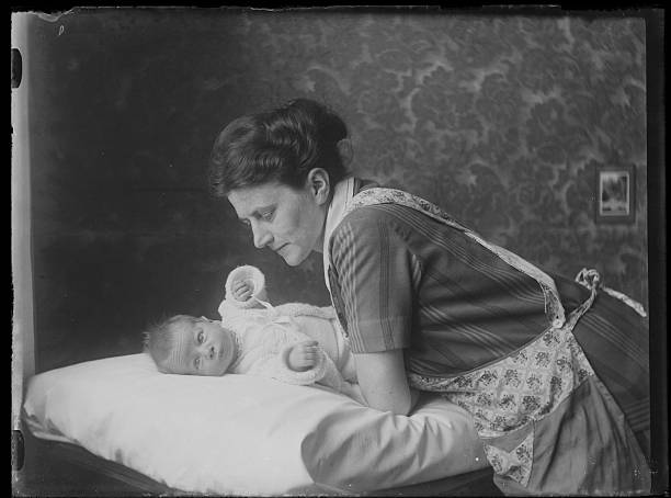 black and white photo of caring mother leaning over her baby - 1920s style stock photos and pictures