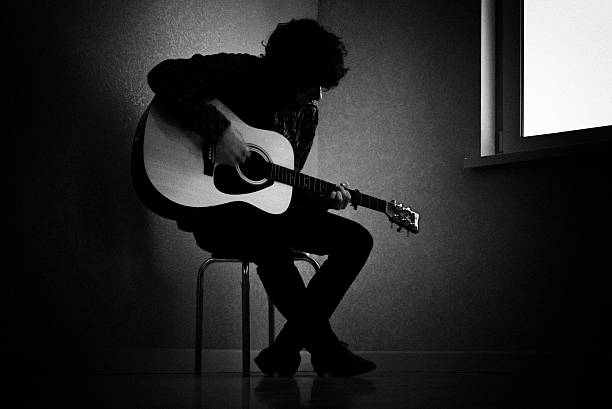Black and white photo of man playing guitar Man sitting on stool in dark room playing guitar guitarist stock pictures, royalty-free photos & images