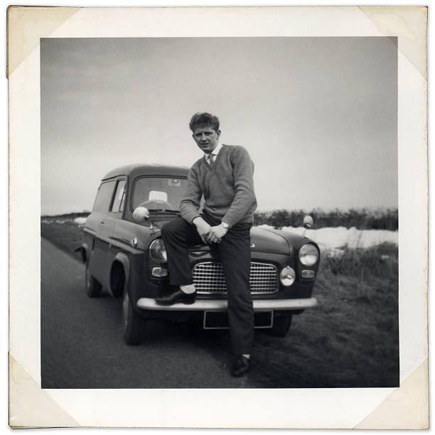 Black and white photo of man sitting on vintage car bonnet stock photo