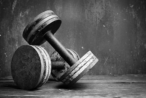 a black and white photo of old dumbbells - weights stock photos and pictures