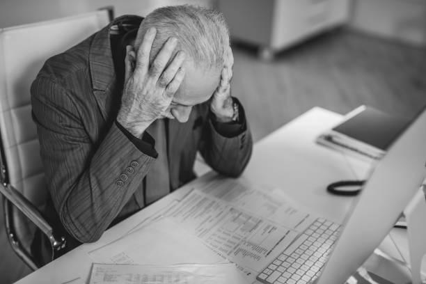 Black and white photo of overworked senior businessman. stock photo