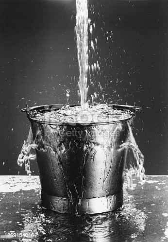 Black and white photo of Water pouring into a bucket