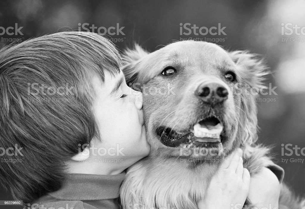 Black and white photo of young boy kissing a dog stock photo