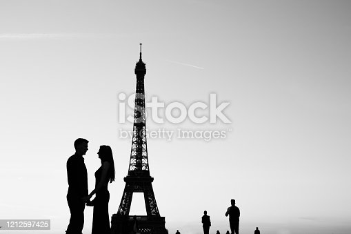Black and white photo, silhouette of couple in love near Eiffel tower in Paris