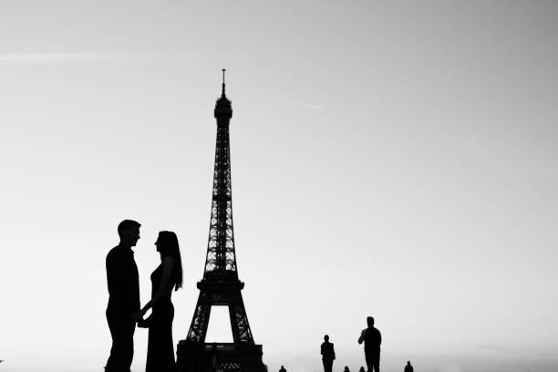 photo noire et blanche, silhouette de couple amoureux près de la tour eiffel à paris - france photos et images de collection
