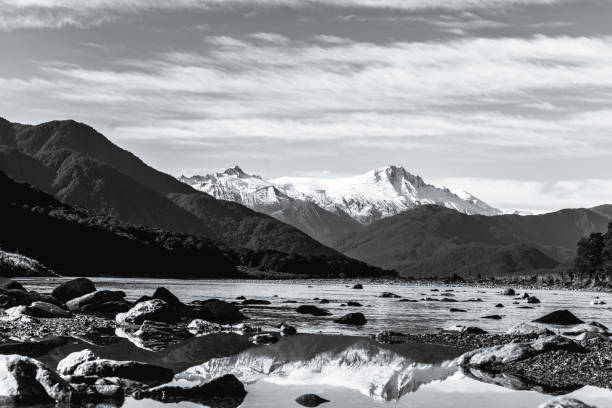 Black and white photo. Stunning landscpae of the reflection of the snow mountain on the river. Blue sky and some cloudy. stock photo